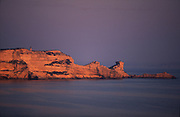"""Cliffs near Bonifacio at sunset..The most famous Corsican Easter procession takes place in Sartène on the evening of Good Friday. A masked penitent, the identity of whom is only known to the local parish priest, acts out the Stations of the Cross. With his feet in chains and wearing a hood and a red vestment, the """"Catenacciu"""" (""""the chained one"""" in the Corsican language) walks through the town carrying his heavy cross amid a contemplative crowd. A ceremony full of religious and mystical fervour. In Bonifacio the Catholic brotherhoods of pilgrims, confraternities, march along the walls of the fortified city for Easter week and in Cargese there is the orthodox monastery's Easter celebrations where shotguns are fired and prayers recited on the cliff edge and in the church. Children collect the empty spent cartridges as souvenirs. Corsica itself is a mixture of steep rocky mountains, ice and snow capped at their highest peaks all year around, isolated villages nestled into the hills, fishing ports, lobster fishermen, and historic sites dating back to neolothic times."""