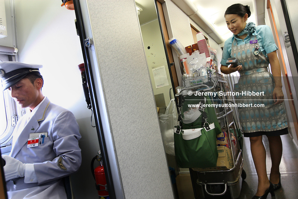 Kumiko Mogi, 27, a 'coffee cart' girl on the JR East Railway bullet trains, Japan, Wednesday, Aug. 22nd, 2007. Kumiko Mogi has been working as a coffee cart girl for 9 years and regularly sells upto five times as much stock (of coffees, food bento boxes, and souvenirs) to train passengers than other 'coffee cart girls'. Mogi-san is one of only 2 Chief Instructors out of a staff of 1,300 women.