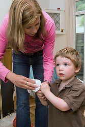 Nanny wiping little boys hands,