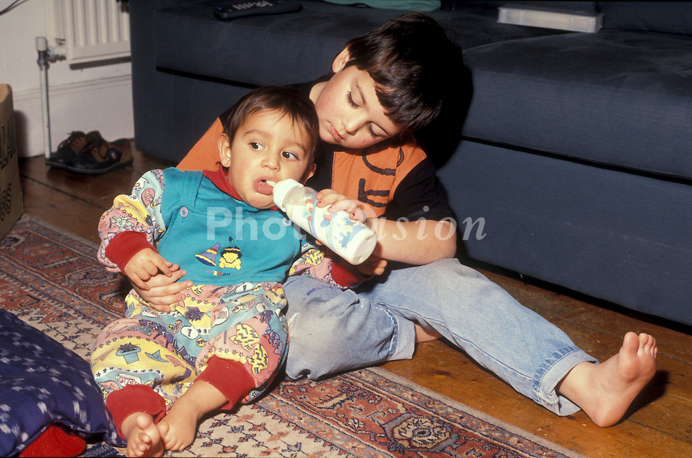 Older brotherfeeding bottle of milk to younger brother