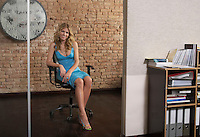 Young woman sitting in chair in office doorway
