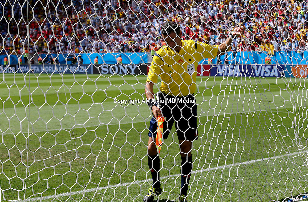 The assistant referee checks the goal net before the match