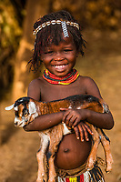 A young Nyangatom tribe girl holds a baby goat (kid), Omo Valley, Ethiopia.