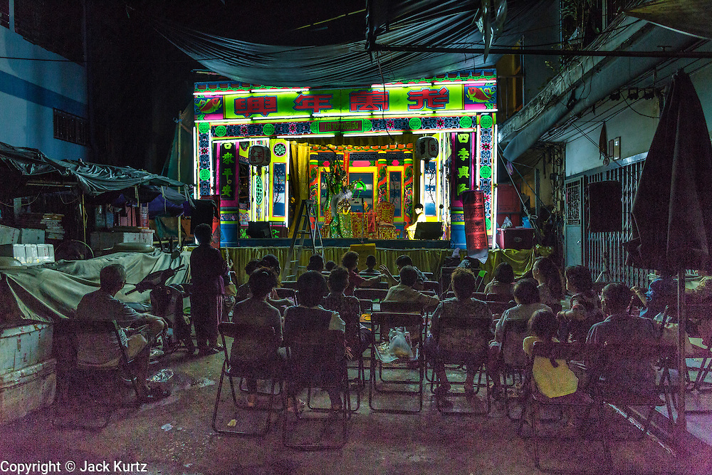 27 APRIL 2013 - BANGKOK, THAILAND:   People watch a Chinese performance in the Talat Noi neighborhood of Bangkok's Chinatown. Chinese opera was once very popular in Thailand and is usually performed in the Teochew language. Millions of Chinese emigrated to Thailand (then Siam) in the 18th and 19th centuries and brought their cultural practices with them. Recently its popularity has faded as people turn to performances of opera on DVD or movies. There are as many 30 Chinese opera troupes left in Bangkok. They travel from Chinese temple to Chinese temple performing on stages they put up in streets near the temple, sometimes sleeping on hammocks they sling under their stage. The opera troupes are paid by the temple, usually $700 to $1000 a night.   PHOTO BY JACK KURTZ