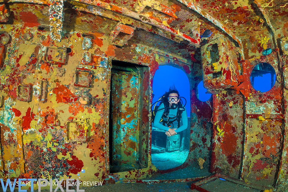 A diver (Marion Morin) swims into the bridge of the wreck of the USS Kittiwake, where the walls are now encrusted in colourful sponges. Seven Mile Beach, Grand Cayman, Cayman Islands, British West Indies. Caribbean Sea.