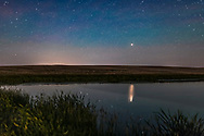Mars is rising and shining a reflected red glitter path on a prairie pond, on June 19, 2018. Mars was 5 weeks away from its closest approach in 15 years and so was very bright, and getting brighter each night. The setting waxing Moon lights the scene plus the sky is bright from solstice twilight. Some bands of airglow colour the sky. Mars is in Capricornus. <br /> <br /> This is a stack of 6 exposures for the ground, mean combined to smooth noise, and one exposure for the sky and reflection. All 25 seconds at f/2 with the 35mm lens and Canon 6D MkII at ISO 800.