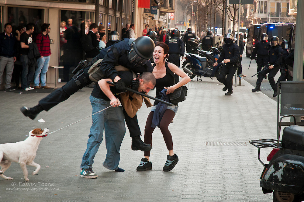 Police charge a crowd of protestors and attack an innocent couple after a few individuals (not this couple) threw rocks at the police. The woman was hit and thrown to the ground while the man was restrained and hit several times by different officers. Once the police realized this couple were not throwing stones they returned to their vehicles, leaving the couple shaken and in tears.