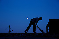 Boy sweeping terrace with full moon on blue sky in background. Every day hundreds of millions of people in India wake up at dawn and work hard until sunset to find their way out of poverty. Many of these people cannot access clean water and electricity, nor pay school fees for their children or see a doctor when they are sick. Their basic needs have been largely unmet, neither by public services nor by the market that doesn't consider them as potential customers. Access to health care services in India by low-income people is limited due to the poor supply from the public service, especially in remote areas such as slums.