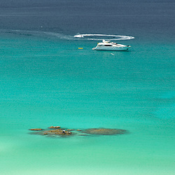 A large luxury yacht and waverunner in a turquoise coral bay in Playa Balandra, Mexico.