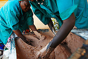 Women beat shea paste by hand to help form emulsion at the Si Yiriwa shea processing center in the town of Diolila, Mali on Friday January 15, 2010.