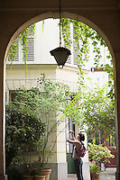 Young woman taking photograph of house view through archway