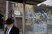 A Jewish gentleman, bus stop graffiti and an ad for the new Aardman Animation's new release Early Man, on 30th January 2018, in the south London borough of Southwark, England.