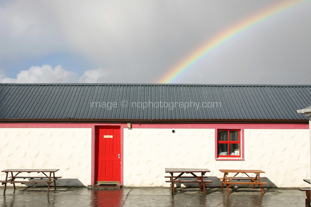 White cottage with rainbow on Inis Mor the Aran Islands, Connemara, County Galway, Ireland.