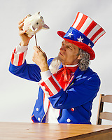Uncle Sam sitting at a table trying to get the last money out of his piggy bank...Model Release: 20080813_MR_A