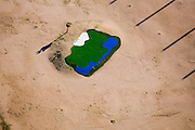 In the middle of a desert landscape sits an isolated patch of an artificial golf course with a simulated pond and sand trap.  Artificial surfaces are used to save water and cut irrigation costs.