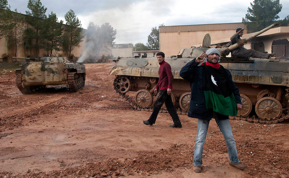 A man salutes as tanks driven by Opposition forces drive past at the Army Depot in Shahat, Libya.