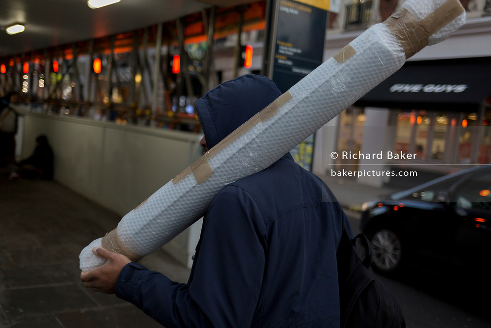 A man wearing a hooded top carries a tube covered in bubble wrap on Long Acre, on 12th December 2017, in London England.