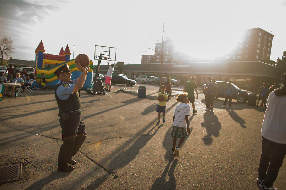 Mississauga , Ontario - August 19, 2015 -- Basketball -- A police officer shoots a ball on a temporary basketball court set up by the Erin Mills Youth Centre during a community event in a parking lot in Mississauga, Thursday August 19, 2015   (Mark Blinch for the Globe and Mail)