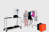 Portrait of senior photographer standing in front of clothes rack and photographic equipments in studio