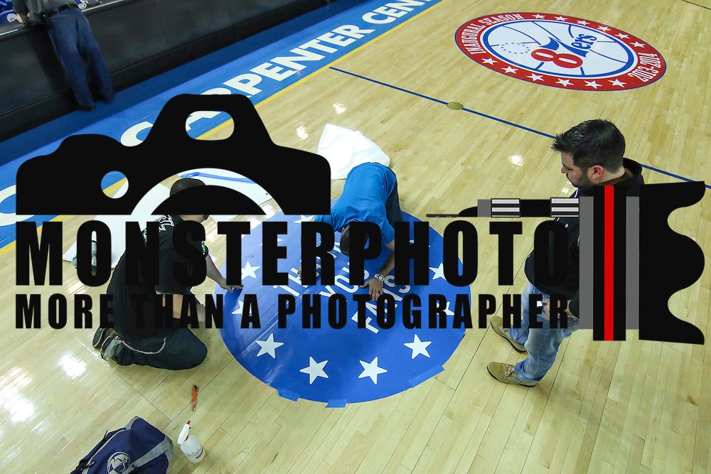 James Personti Jr. ,LEFT, and Jon Gleber, CENTER, and Jason Gleber of unique Images of Wilmington Delaware place decal on the court in preparation for a Saturday NBA D-league regular season basketball game between the Delaware 87ers (76ers) and Springfield Armor (Brooklyn Nets) Friday, Apr. 04, 2014 at The Bob Carpenter Sports Convocation Center, Newark, DEL.