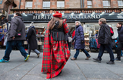 Woman wearing tartan handing out flyers to tourists at tourist gift shop on the Royal Mile in Edinburgh, Scotland, united Kingdom