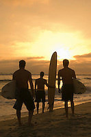 Three surfers standing on beach holding surfboards watching sunset back view