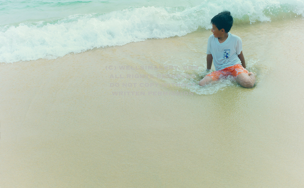 Image of a little boy playing on the beach in Cabo san Lucas, Baja California Sur, Mexico
