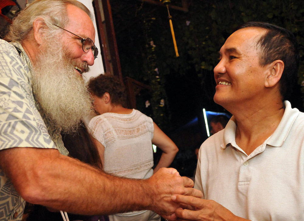 Charlie Forsyth thanks Tran Dinh Song with a token of his appreciation at a farewell meal in HoiAn, Vietnam.  Song, a drafted veteran of the war, acted as our tour guide, translator, war historian, friend, and honorary member of Warriors Journey Home..(Laura Fong Torchia / Special to the Beacon Journal)
