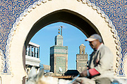 FEZ, MOROCCO - 1st DECEMBER 2016 - Person on horseback rides past the Bab Boujloud / Bab Bou Jeloud / the blue gate with Mosque minarets in background, old Fez Medina, Middle Atlas Mountains, Morocco.