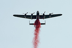 © London News Pictures. 28/06/2012.  London, UK. An RAF Lancaster Bomber dropping a million poppies over the memorial during the unveiling of a new £3.5m Bomber Command Memorial in Green Park, London on June 28, 2012. The memorial which is dedicated to the 55,573 airmen who died in the Second World War is made of Portland Stone stands at over 8m tall with an open roof. The entrance is made from melted down aluminium sections of a Halifax bomber shot down during the war and in which all seven of the crew were killed. The memorial includes inscriptions from Winston Churchill. Photo credit: Ben Cawthra/LNP