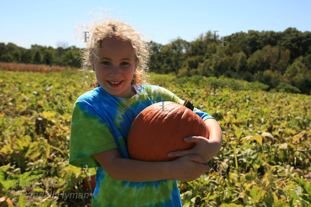 Nine-year-old girl hugs perfect pumpkin in pick-your-own pumpkin patch at Eckert's farms near Grafton, Illinois.