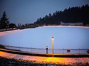 Fresh snow on frozen-over Reservoir 5, Mount Tabor Park, Portland, Oregon, USA.