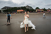 BALI, INDONESIA; APRIL 23, 2015: A couple from China have a pre-wedding photo shoot at Double Six beach, Bali, Indonesia on Thursday, April 23, 2015.