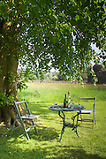 Table and Chairs with bottle of wine under tree in theorchard at Tynron Garth, Tynron.
