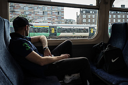 © Licensed to London News Pictures. 10/08/2016. London, UK. A man on a train into London's Victoria Station as a Southern Rail train passes by. Southern Rail staff have called off the final two days of a week-long strike over job losses and passenger safety. Photo credit: Rob Pinney/LNP