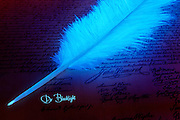 A glowing pen rests on the Declaration of Independence with Doctor Blacklight signature written in glowing ink.Black light
