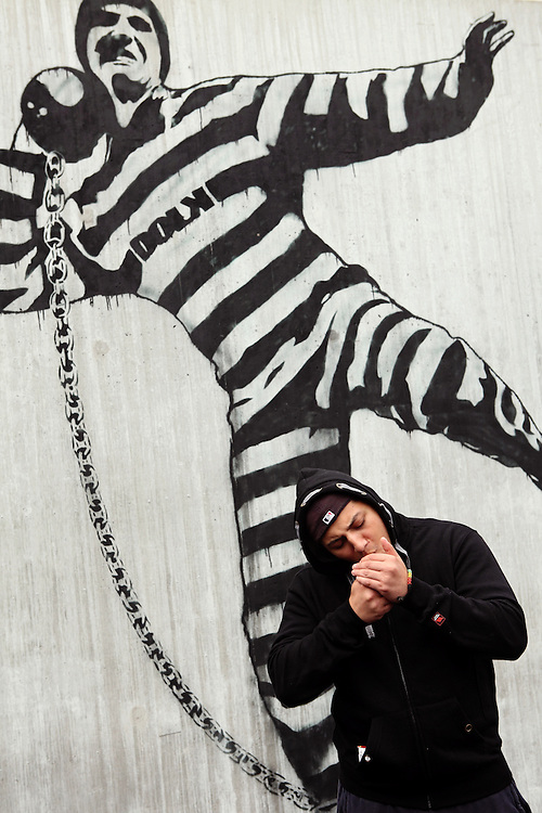 A young convict is smoking a cigarette next to one of the graffiti commissioned to Dolk, a renowned Barsky-type Norwegian artist, in the luxurious Halden Fengsel, (prison) near Oslo, Norway.
