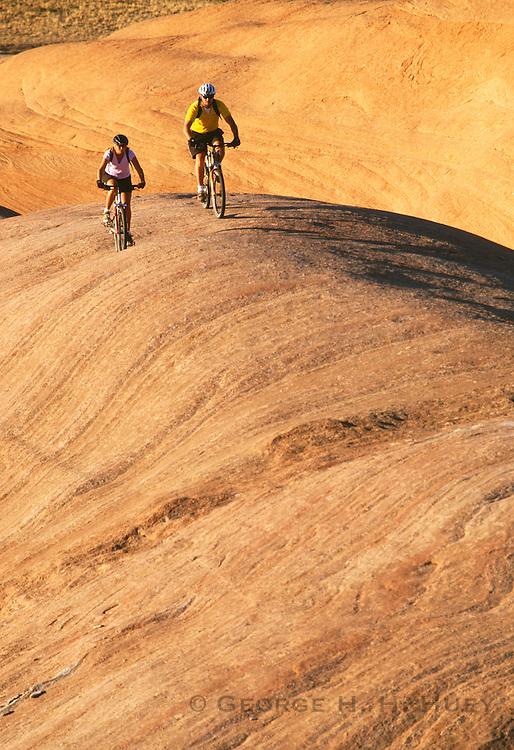 350361-1005B ~ Copyright: George H. H. Huey ~ Male & female mountain bikers on the Moab Slickrock Bike Trail. Bureau of Land Management area.  Best known bike trail in Southern Utah.  Moab, Utah.