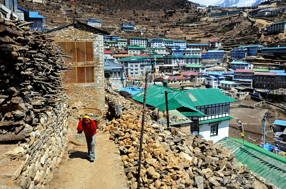 Nepal, Namche Bazaar. Girl from Namche Bazaar (3400 m above see level)  carrying a basket.