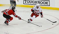 Apr 15, 2009; Newark, NJ, USA; New Jersey Devils defenseman Colin White (5) plays defense against Carolina Hurricanes right wing Erik Cole (26) during the second period of game one of the eastern conference quarterfinals of the 2009 Stanley Cup playoffs at the Prudential Center.