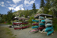 Kayaks remain stored and ready for the next group of paddlers that will learn the necessary skills of how to Kayak at Strathcona Park Lodge, a popular outdoor school facility located on Central Vancouver Island.  Vancouver Island, British Columbia, Canada.