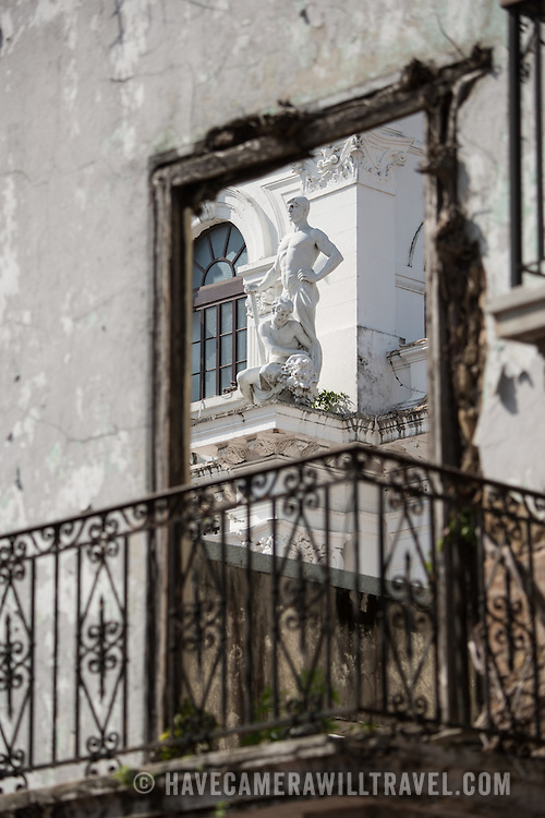A statue on the old City Hall of Panama City in the heart of Casco Viejo fronting Independence Plaza, as seen through a doorway of a rundown shell of a building next door.