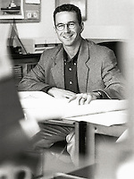 Businessman sitting at desk, portrait (B&W)