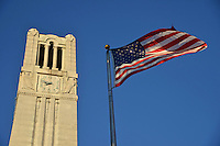 Early morning sun cuts across the Memorial Belltower and the American flag.