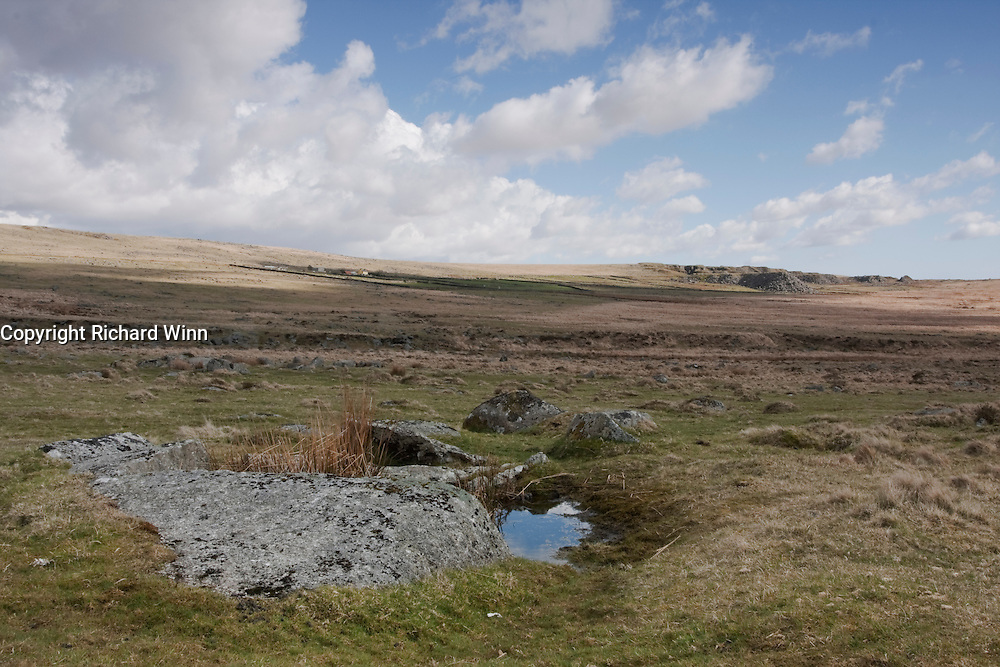View of the quarry to the east of King's Tor from its base, with a bog pool in the foreground.