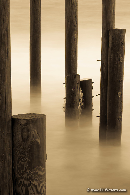 This sepia tone  picture of the Outer Banks, Kitty Hawk pier was taken with a very long shutter speed. The movement of the waves has blurred across the image to make it look like fog.