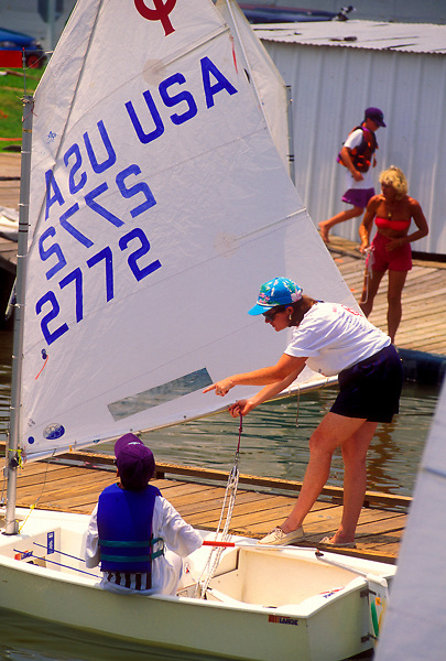 Stock photo of a woman checking the sail on a boy's boat