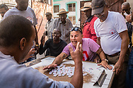A heated domino match takes place in the streets, amidst accusations of cheating from all players. Downtown Havana, Cuba.