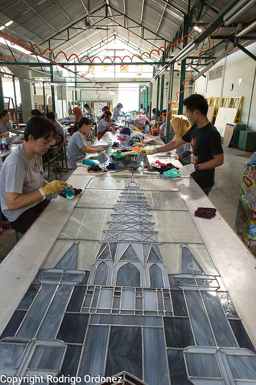 Employees apply chemical products to a stained glass window in the form of a church at the Eztu Glass factory in Tangerang, near Jakarta, Indonesia, on July 2, 2015. Indonesia is the country with the world's largest Muslim population, of about 205 million people. Roughly 88% of Indonesia's population is Muslim, and the nation is home to about 13% of the world's Muslims.