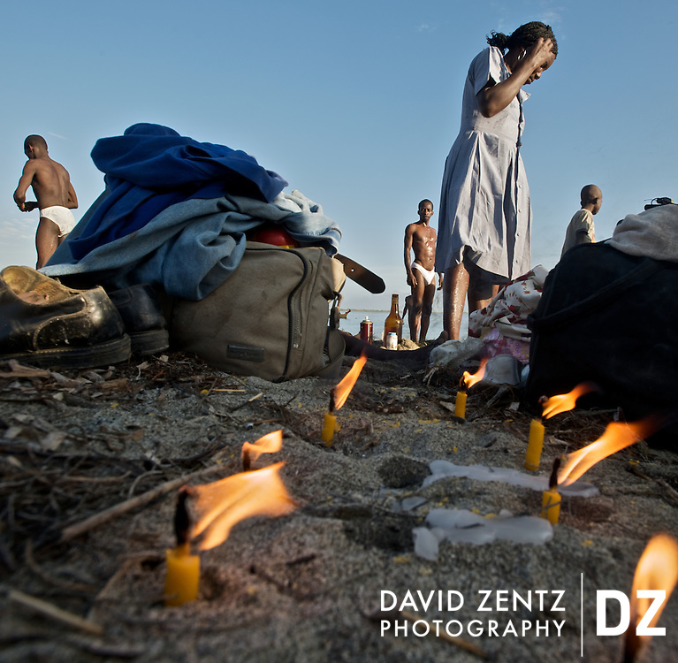 Candles lit to summon different lwa - or spirits - sit in the sand as pilgrims move about the beach and cleanse themselves in the sea during a sunrise voodou ritual at Bord de Mer de Limonade, on the north coast of Haiti on July 25, 2008. After renewing their faith in the mud pit at Plaine du Nord on the days prior, pilgrims migrate to the nearby water, their faith renewed.